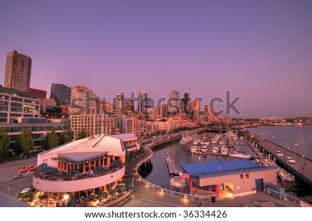 Wide angle view of the city of seattle with its tall buildings, restaurants, streets, and boats in waterfront docks - stock photo