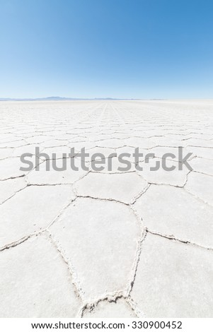 Wide angle view of the world famous Uyuni Salt Flat, among the most important travel destination in the Bolivian Andes. Close up of hexagonal shapes of the salt pans.  - stock photo