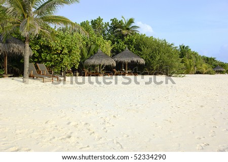 wide beach with sun loungers and parasols - stock photo
