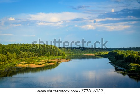 wide calm river under the blue sky - stock photo