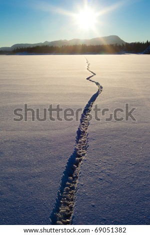 Wide crack in snow-covered ice surface of frozen lake. - stock photo