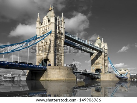 Wide daytime shot of Tower Bridge, London, UK, with a black and white background and the bridge in color  - stock photo