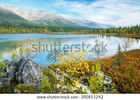 Wide epic view of Hibiny mountain ridge reflected in azure water of Polygonal lake with birch and spruce trees on the foreground, Kola peninsula above the Arctic Circle, Russia - stock photo