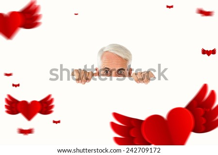 Wide eyed man showing large poster against hearts - stock photo