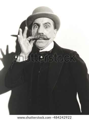 Wide-eyed man touching his mustache