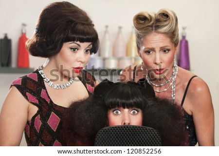 Wide eyed woman behind mirror with two friends in hair salon - stock photo