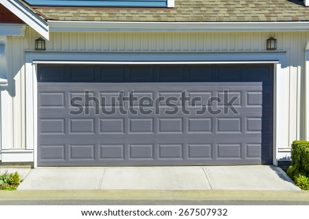Wide garage door of residential townhouse on sunny day, British Columbia, Canada. Double garage of family townhouse with concrete driveway.