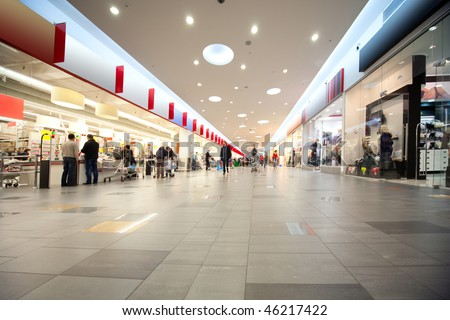 Wide hall and buyers in trading center with shops on both sides - stock photo