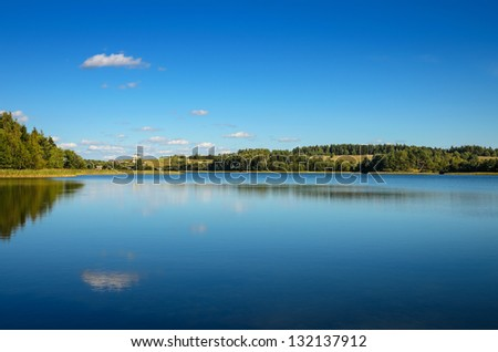 wide lake under bright blue sky - stock photo