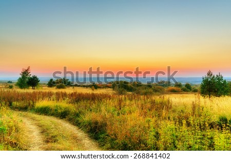 Wide landscape beneath clear evening sky and dawn - stock photo