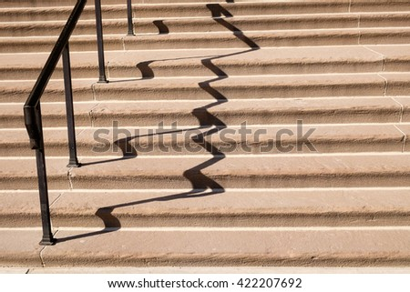 Wide limestone staircase with iron railing and clear shadow  - stock photo