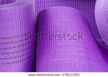 Wide nylon flat rope stitched with thread wound into a roll  background lilac