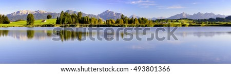 wide panorama landscape in Bavaria with alps mountains and lake