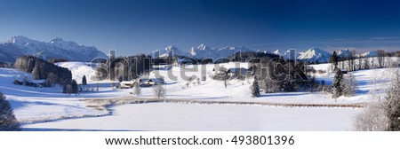 wide panorama landscape in Bavaria with alps mountains and lake in winter with fresh snow
