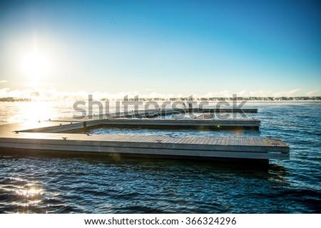 Wide panorama of lake huron with dock and muskoka chairs at sunrise - stock photo