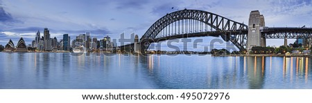 WIde panorama of Sydney city landmarks across harbour from  house to Harbour bridge with CBD skyscrapers in between.