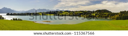 wide panorama view over a lake to alps mountains in bavaria, germany - stock photo