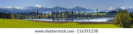 wide panorama view over lake Forggensee in region Allgaeu to alps mountains in bavaria, germany