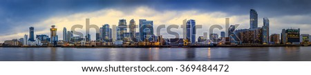 Wide panoramic skyline of Canary Wharf, the worlds leading financial district at blue hour - London, UK - stock photo