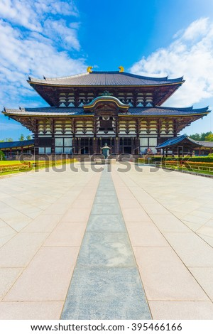 Wide path leading to front exterior facade of Great Buddha Hall, Daibutsuden, nobody present, on sunny, blue sky morning in Todai-ji temple empty of people in Nara, Japan. Vertical copy space - stock photo