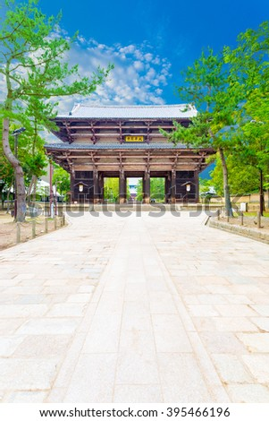Wide path to great south gate, nandaimon, with nobody present at Todai-ji temple complex on beautiful sunny, blue sky summer day in Nara, Japan (foreign text: yellow sign Dai Kegon Temple)