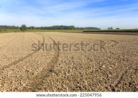 Wide plowed brown field with tractor tire tracks and traces - stock photo