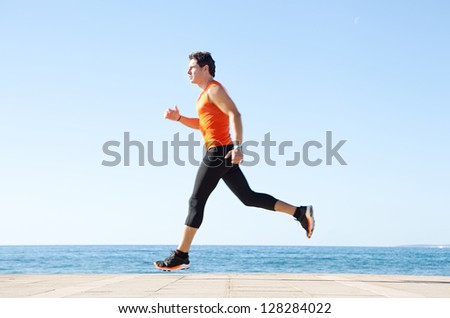 Wide profile view of a sports man running figure on a track along the sea with the blue sky in the background and space around him. - stock photo