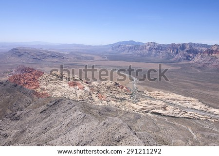 Wide scenic high angle view of Red Rock Canyon, Nevada under clear blue sky with colored rock formations seen from top of Turtle Head Peak - stock photo