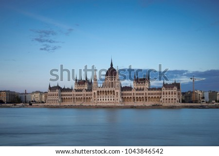 Wide shot of the Hungarian Parliament on the River Danube Budapest. Taken from the opposite bank of the river during twilight