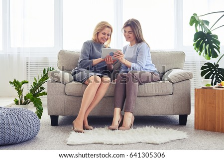Wide shot of women in fashionable clothes surfing on Internet in laptop