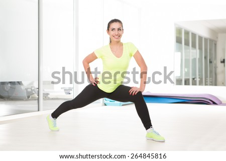 Wide step. Beautiful sporty woman in gym - stock photo