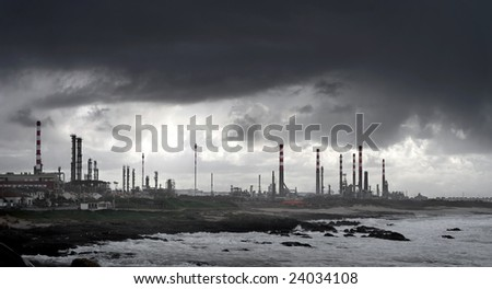 Wide view of a petrochemical complex under a stormy sky. - stock photo