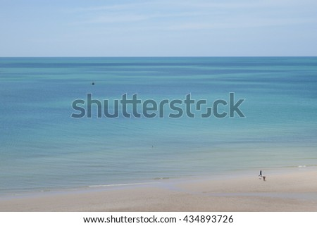 Wide view of beautiful sea beach with two people walking and strolling along in summer holiday time - background