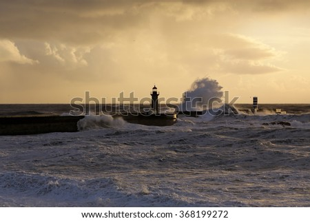 Wide view of big stormy sea waves over pier and lighthouses at winter sunset. Entry of Douro river mouth harbor, north of Portugal. Soft backlighting. - stock photo