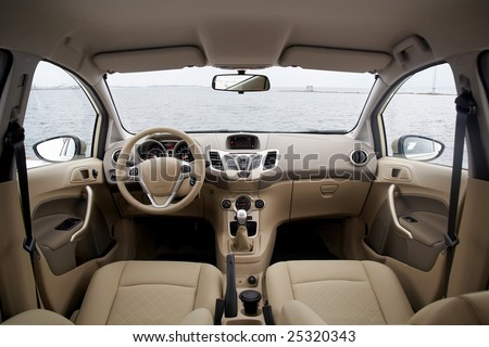 Wide view of modern car interior with light-colored decoration - stock photo