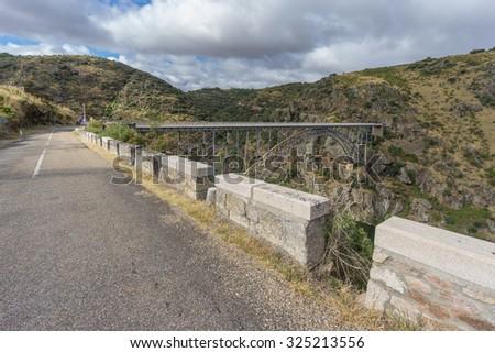 Wide view of road to Requejo iron Bridge in Pino del Oro, Castile and Leon, Spain - stock photo