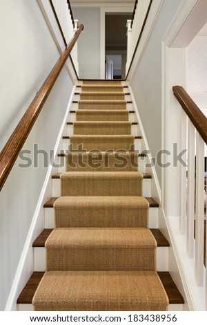 Wide View of wooden staircase with carpet runner and white molding.  - stock photo