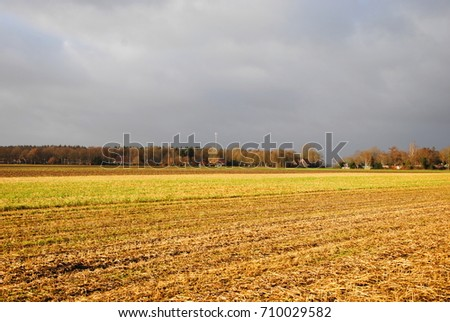 Wide view on farmland fields under a threatening sky in winter in rural Groningen, one of the northern provinces of the Netherlands