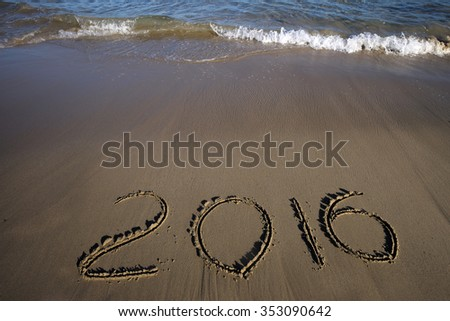 Wide view on ocean or sea beach marine coast with blue wavy clean water and hand drawn date of new 2016 year or christmas on yellow sand sunny day outdoor on natural background, horizontal picture - stock photo