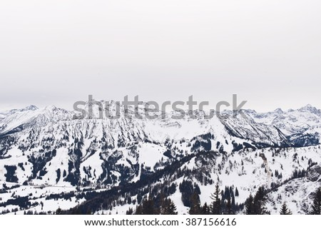 Wide view under overcast sky and forested snow covered mountain range and foothills - stock photo