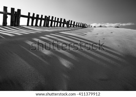 Wide vue of a sea sand dune near a beach with wood fences. Beautiful shadows in the foreground. Portugal. Black and white. Soft backlight. - stock photo