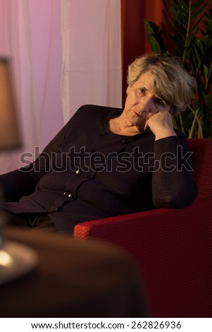 Widow suffering for depression sitting in armchair - stock photo