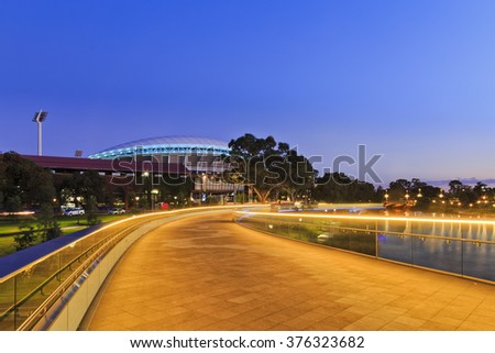 width of modern footbridge over Torrens river in Adelaide, South Australia. Bright illumination lights reflecting in calm waters at sunrise