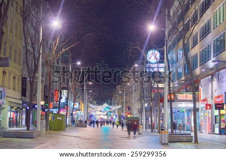 WIEN, AUSTRIA, JANUARY 4, 2015: people are walking through illuminated, christmas decorated mariahilfestrasse street in the center of wien. - stock photo