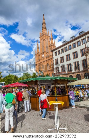 WIESBADEN, GERMANY - AUG 8, 2011: people enjoy the vine festival at central market place in Wiesbaden, Germany. The market takes place in front of the Market church fromNew town hall from 1862.