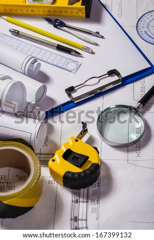 Wiew on a typical engineer workplace with blueprint and measuring tools vertical - stock photo