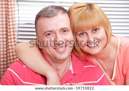 Wife and husband in middle age hugging and smiling - stock photo