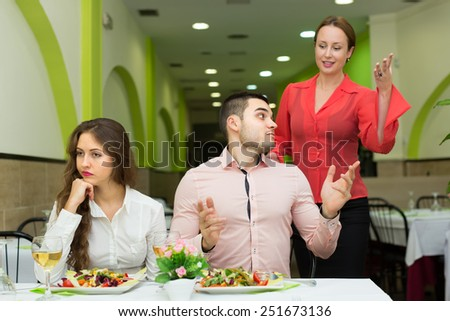 Wife caught husband having dinner in cafe with young mistress. Focus on man  - stock photo