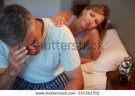 Wife Comforting Husband Suffering With Insomnia - stock photo