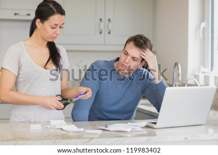 Wife cutting up credit card with husband watching in kitchen with laptop - stock photo
